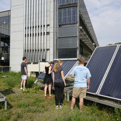 Schüler betrachten Solarzellen