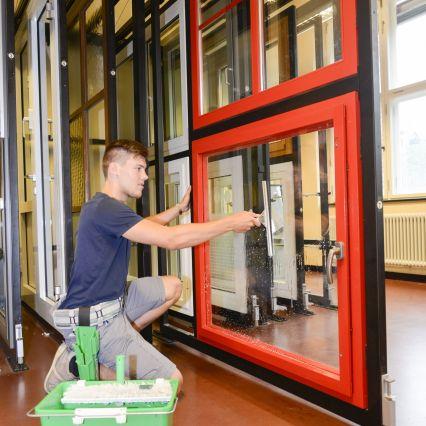 Schüler reinigt eine Fensterscheibe